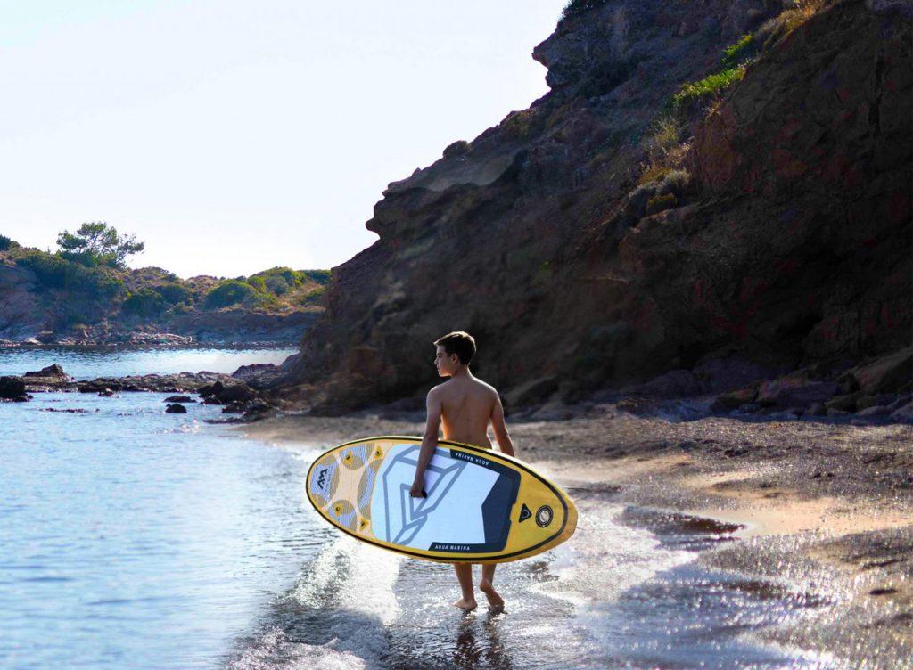 Młody chłopak idzie z żółtą deską brzegiem plaży. Plaża piaszczysto kamienista. Błękitne niebo.